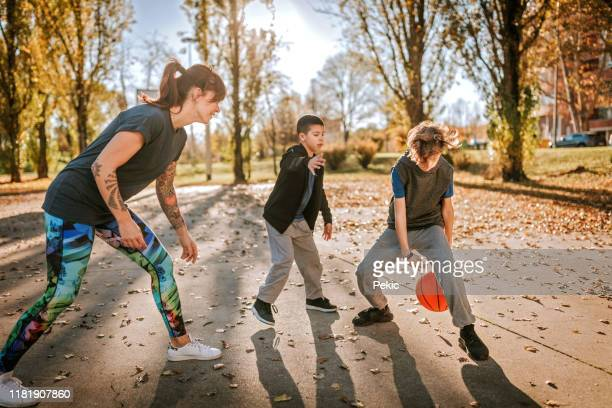 tattooed woman having fun with sons on basketball field - sporting term stock pictures, royalty-free photos & images