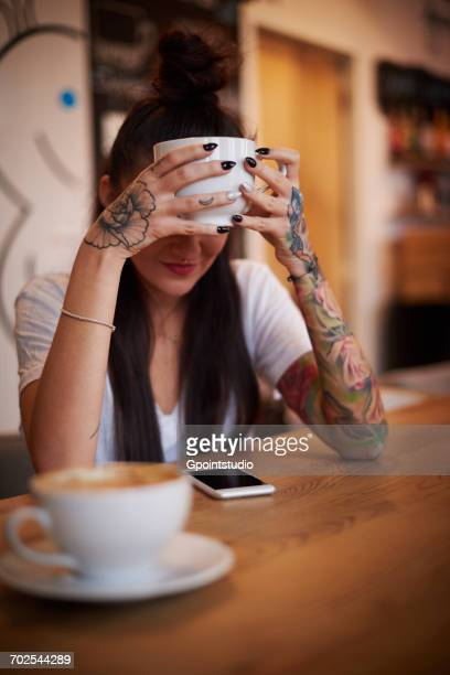 Tattooed woman holding cup looking down at smartphone