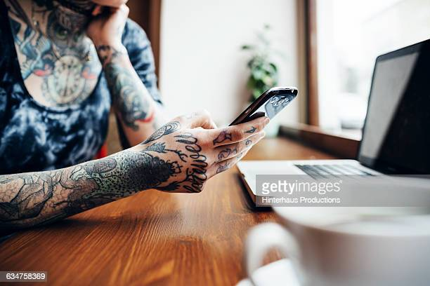 Tattooed woman holding her smart phone