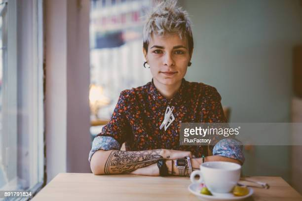 Tattooed woman in a cafe