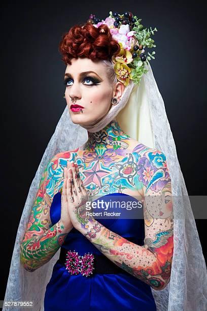 tattooed woman in a veil praying - avondjurk stockfoto's en -beelden