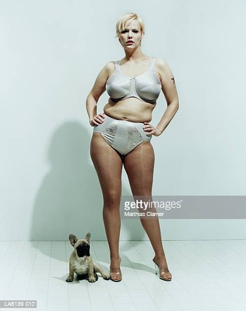 Tattooed woman in underwear standing beside dog, portrait