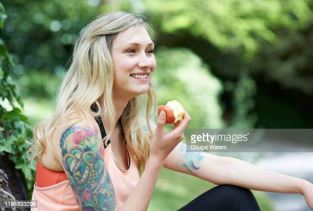 tattooed woman sitting in countryside eating apple. - tattoo stock pictures, royalty-free photos & images