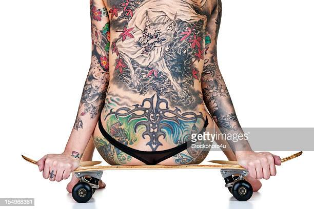 Tattooed woman sitting on skateboard