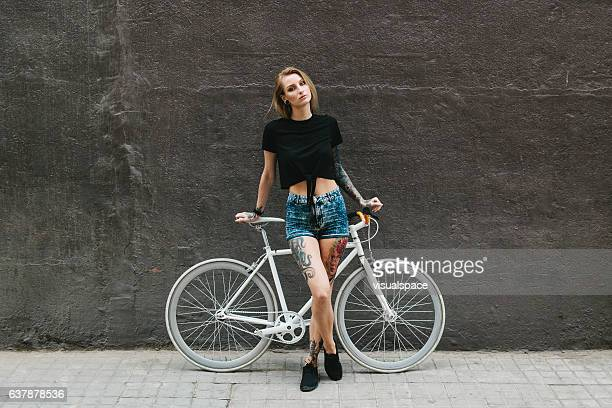 Tattooed Woman Standing in front of White Bicycle