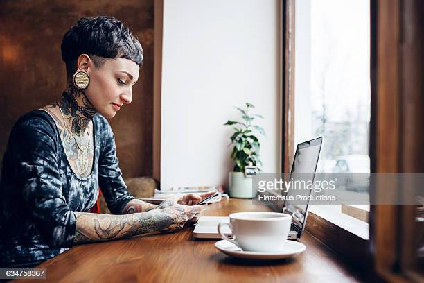 Tattooed woman typing on her smart phone