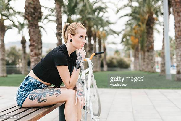 Tattooed Woman with a Bicycle Sitting on a Bench