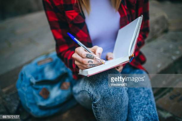 Tattooed womans hand writing in notebook, close-up