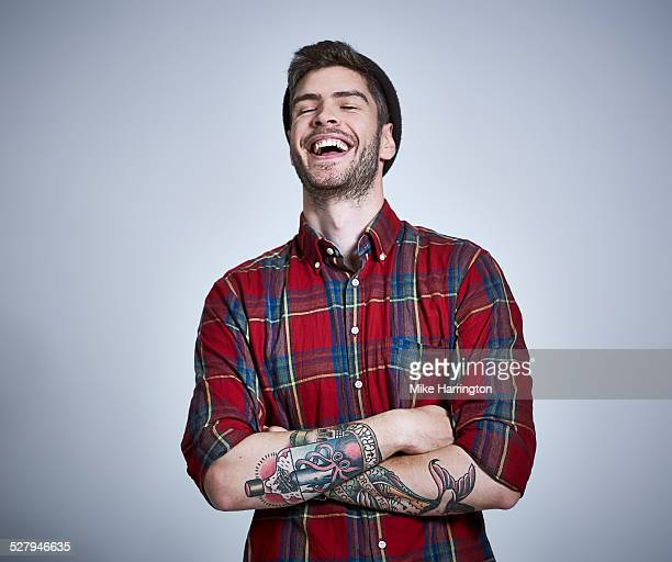 tattooed young male in check shirt laughing. - 25 30 anos - fotografias e filmes do acervo