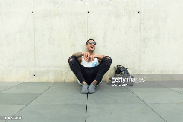 tattooed young man with roller skates sitting on ground having fun - inline skate stock photos and pictures