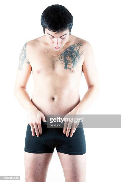 Tattooed Young sexy handsome man looking in his pants