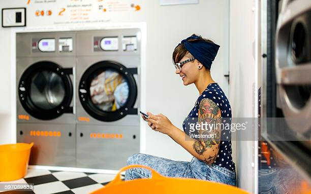 Tattooed young woman looking at her smartphone in a launderette