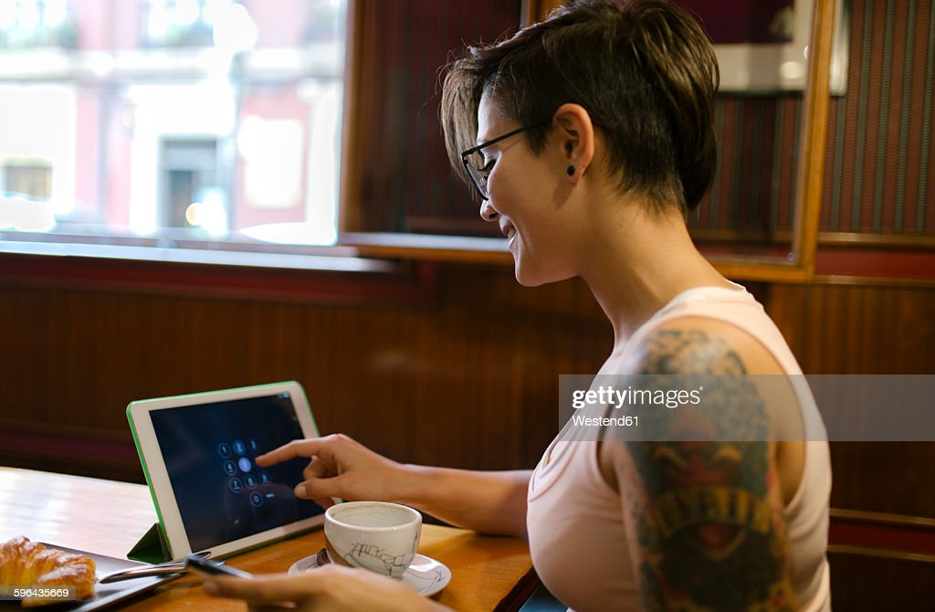 Tattooed young woman sitting in a coffee shop using digital tablet : Stock Photo
