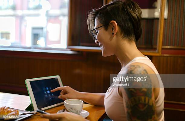 Tattooed young woman sitting in a coffee shop using digital tablet