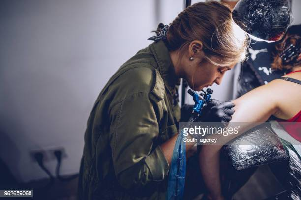 tattooing process - tattooing stock photos and pictures
