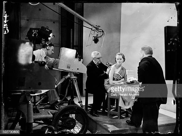 Tattooist at work in a television studio 1938 A photograph of a man being filmed tattooing a woman in a television studio taken by Sayers for the...