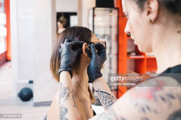 tattooist piercing ear of customer in parlour - piercing stock photos and pictures