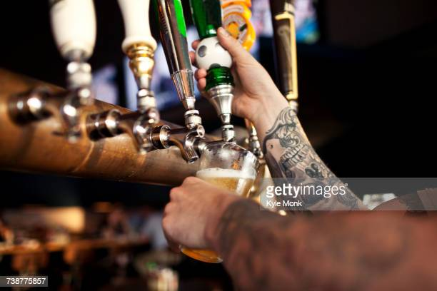 Tattoos on arm of bartender pouring beer