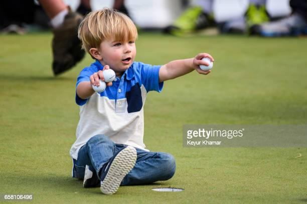 Tatum Johnson son of Paulina Gretzky and Dustin Johnson plays with golf balls on the 18th hole green after his dad's 1up victory during the...