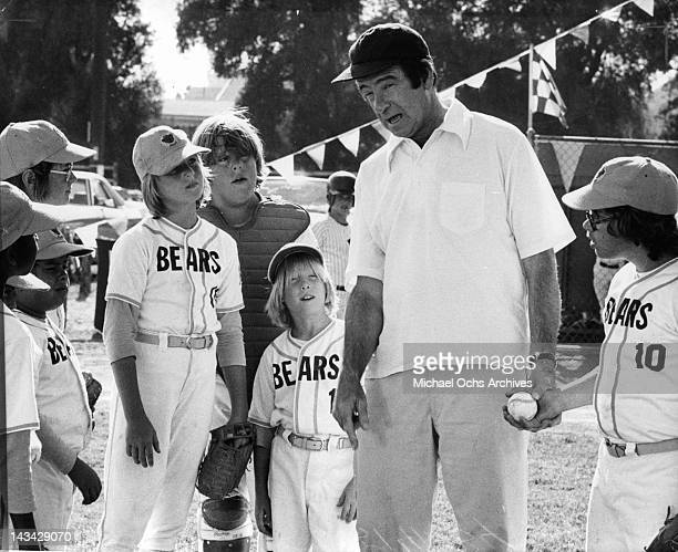 Tatum O'Neal standing with her baseball team looking at Walter Matthau as he explains the game plays in a scene from the film 'Bad News Bears' 1976