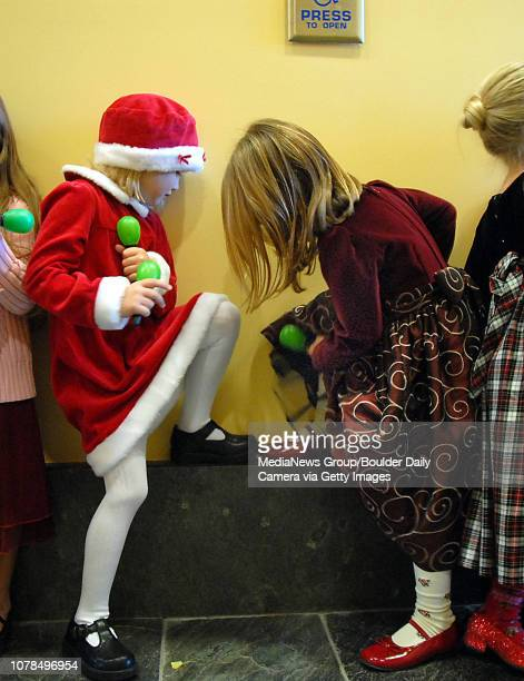 Tatum Roque left compares shoes with Rachel Hirschman after singing Feliz Navidad with their class at the City of Broomfield early learning holiday...