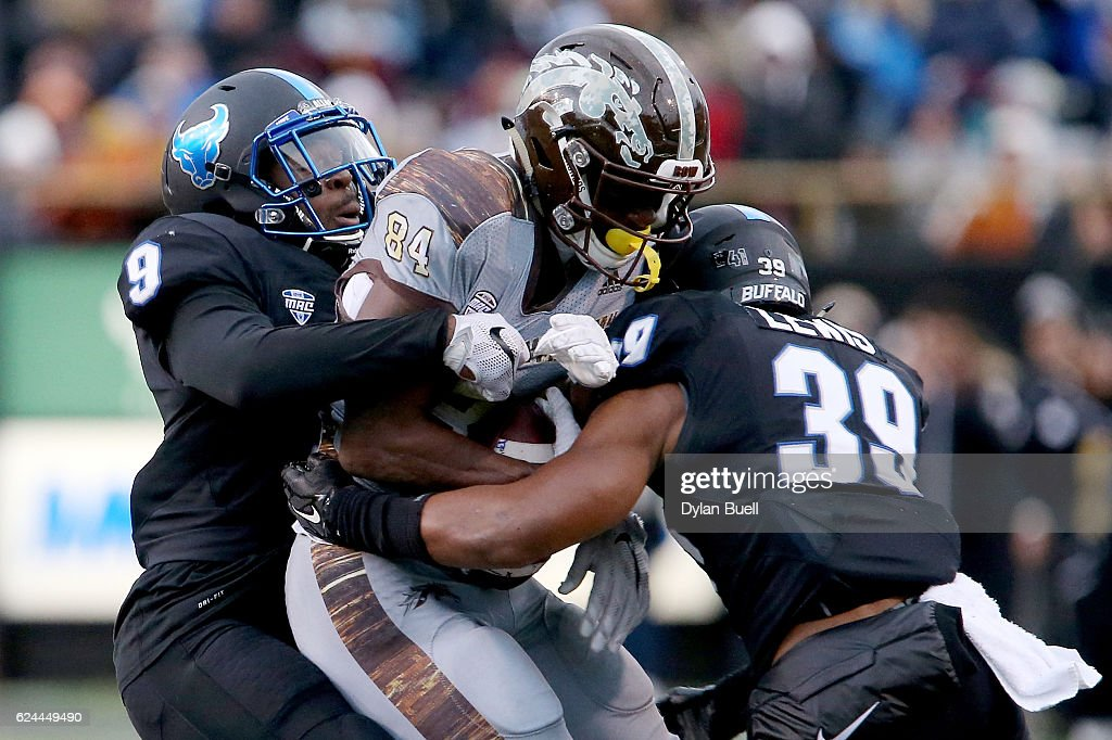 Tatum Slack #9 and Cameron Lewis #39 of the Buffalo Bulls tackle Corey Davis #84 of the Western Michigan Broncos in the first quarter at Waldo Stadium on November 19, 2016 in Kalamazoo, Michigan.