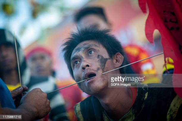 Tatung piercing metal needles through his cheeks during Festival Cap Go Meh celebration on Thusday Singkawang Kalimantan Indonesia The ancient art of...