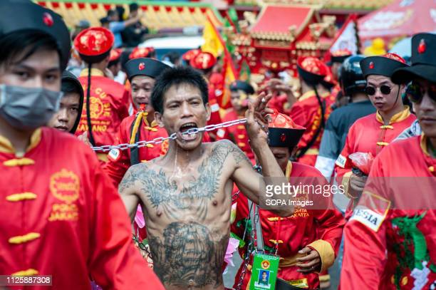 Tatung seen piercing iron chain through his cheeks during the Cap Go Meh festival celebration The ancient art of Tatung which is a part of the Cap Go...