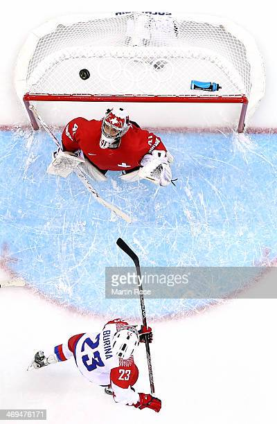 Tatyana Burina of Russia watches the puck fly over Florence Schelling of Switzerland during the Women's Ice Hockey Playoffs Quarterfinal game on day...