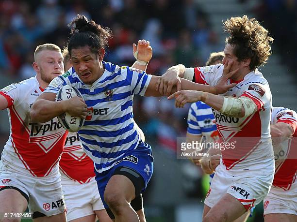 Taulima Tautai of Wigan Warriors holds off a challenge from Louie McCarthyScarsbrook of St Helens during the First Utility Super League match between...