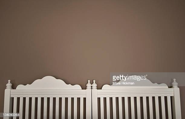 Taupe colored wall with two headboards underneath