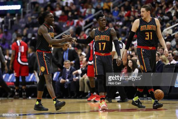 Taurean Prince Dennis Schroder and Mike Muscala of the Atlanta Hawks walk off the floor during a timeout in the first half against the Washington...