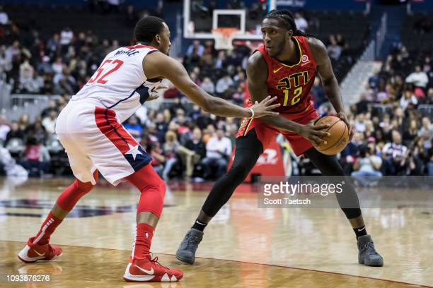 Taurean Prince of the Atlanta Hawks handles the ball against Jordan McRae of the Washington Wizards during the second half at Capital One Arena on...