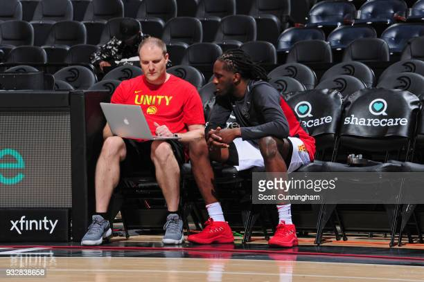 Taurean Prince of the Atlanta Hawks watches film with his coach before the game against the Charlotte Hornets on March 15 2018 at Philips Arena in...