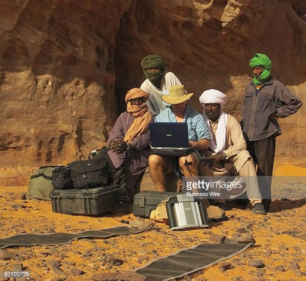 Taureg guides are fascinated by photographer John Canning's laptop computer during Libya desert trek on July 20 2004 Two recent American expeditions...