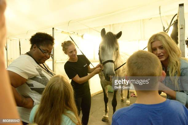 Taurus Bush with the kids feeding the horses at Odysseo on September 21 2017 in Nashville Tennessee