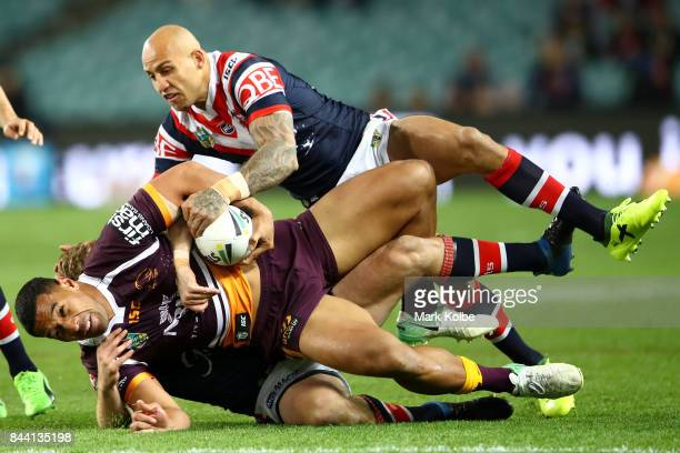 Tautau Moga of the Broncos is tackled by Mitchell Aubusson and Blake Ferguson of the Roosters during the NRL Qualifying Final match between the...