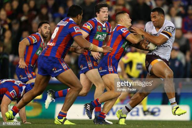 Tautau Moga of the Broncos is tackled by the Knights defence during the round 19 NRL match between the Newcastle Knights and the Brisbane Broncos at...