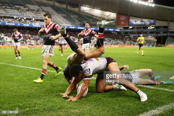 Tautau Moga of the Broncos scores the final try as Blake Ferguson of the Roosters defends during the round 13 NRL match between the Sydney Roosters...