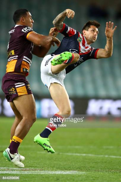 Tautau Moga of the Broncos tackles Mitchell Pearce of the Roosters as he kicks during the NRL Qualifying Final match between the Sydney Roosters and...