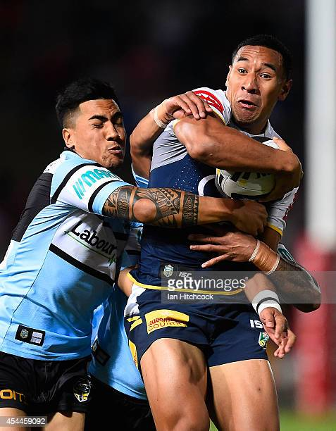 Tautau Moga of the Cowboys is tackled by Sosaia Feki and Ricky Leutele of the Sharks during the round 25 NRL match between the North Queensland...