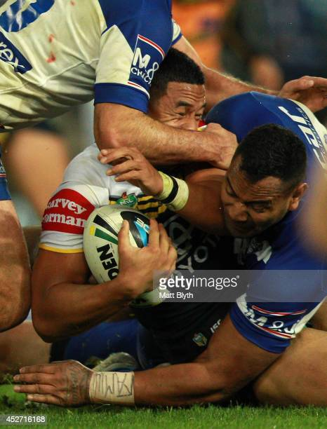 Tautau Moga of the Cowboys is tackled during the round 20 NRL match between the Canterbury Bulldogs and the North Queensland Cowboys at ANZ Stadium...
