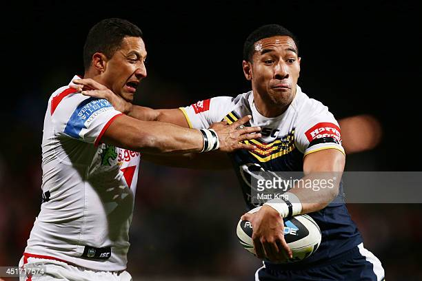 Tautau Moga of the Cowboys puts a fend on Benji Marshall of the Dragons during the round 17 NRL match between the St George Illawarra Dragons and the...