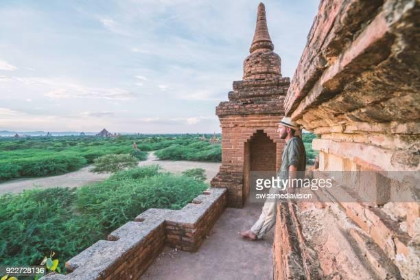 Taveler man contemplating the Bagan archeological zone at sunrise, Burma