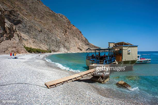 A tavern build on rocks in the sea at Sweetwater Beach between the villages of Hora Sfakion and Loutro on the southern coast of the Greek island of...