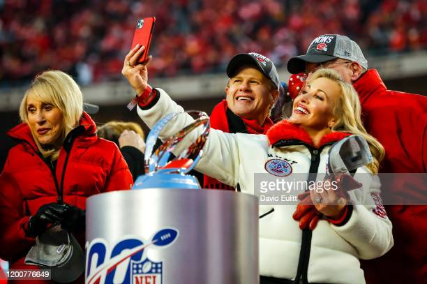 Tavia Hunt and her husband Clark Hunt chairman of the Kansas City Chiefs take a selfie with head coach Andy Reid of the Kansas City Chiefs before...