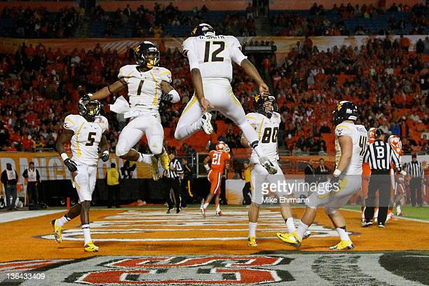 Tavon Austin and Geno Smith of the West Virginia Mountaineers celebrate after Austin caught a 37-yard touchdown reception thrown by Smith in the...
