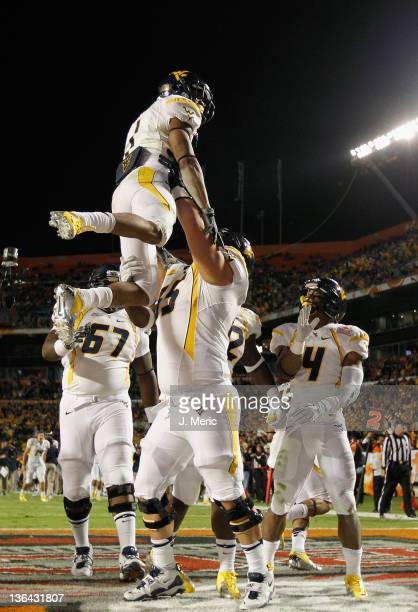 Tavon Austin of the West Virginia Mountaineers is lifted up by Chad Snodgrass as they celebrate with teammates in after Austin scored a 1-yard...