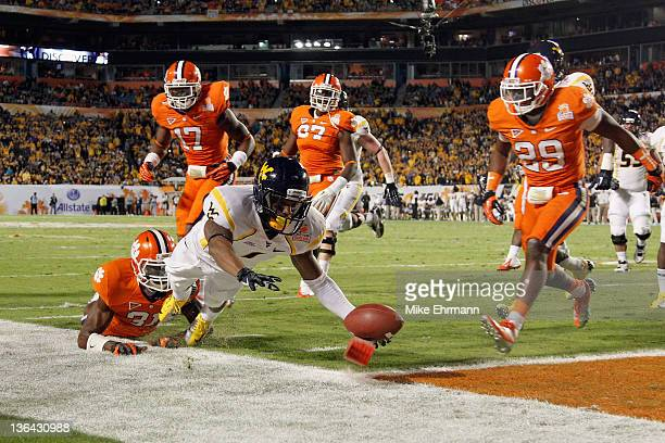 Tavon Austin of the West Virginia Mountaineers scores an 8-yard rushing touchdown in the first quarter against Bashaud Breeland of the Clemson Tigers...