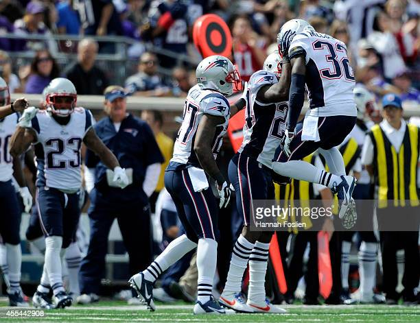 Tavon Wilson and Devin McCourty of the New England Patriots congratulate teammate Darrelle Revis on an interception during the second quarter of the...